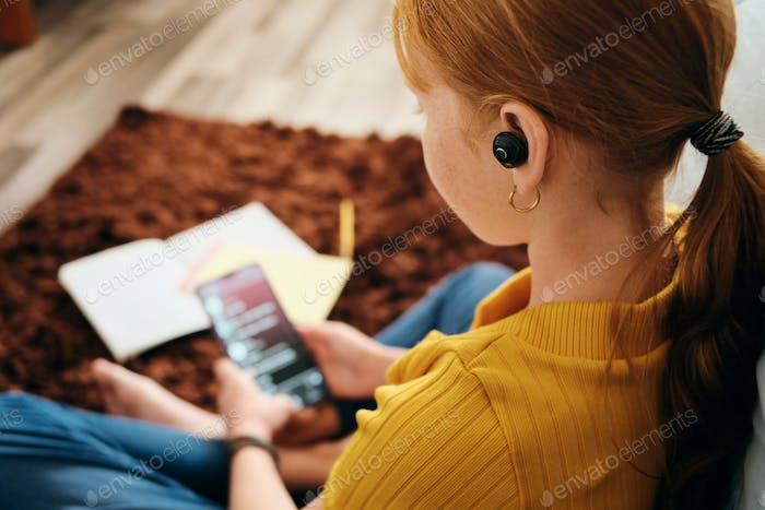 Preteen Mädchen hören Musik mit drahtlosen Ohrhörern