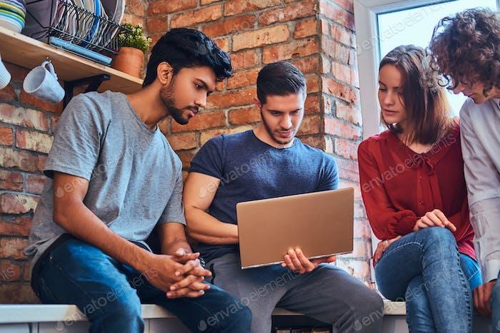 Gruppe von interracial Studenten mit Laptop und Buch tun Unterricht im Studentenwohnheim.