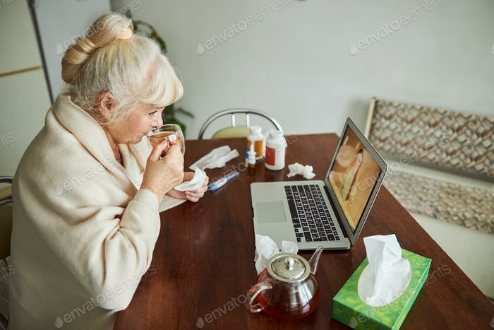 Old woman drinking tea and having online consultation with doctor