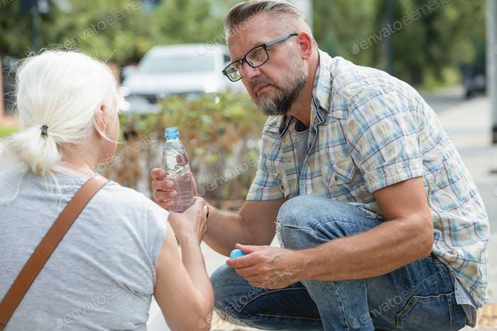 Mittelalter Mann gibt eine Flasche Wasser zu einer Frau, die auf der Straße in Ohnmacht gefallen