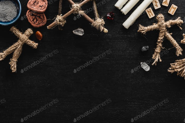 Top View of Voodoo Dolls Near Bowl With Ashes, Crystals, Candles And Old Runes on Black