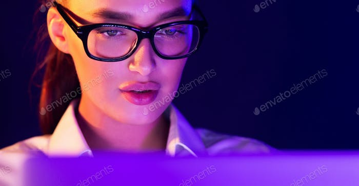 Young woman working on laptop late at night