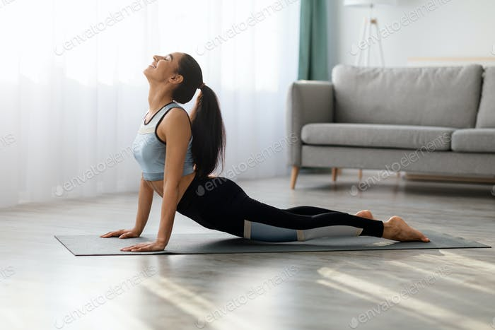 Flexible young woman practicing yoga at home