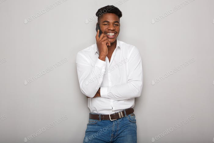 happy african american man talking on cellphone by gray wall