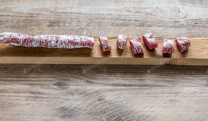 Cut spanish salami on the wooden board