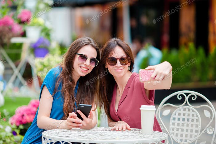 Two young girls taking selfie with smart phone at the outdoors cafe. Two women after shopping with