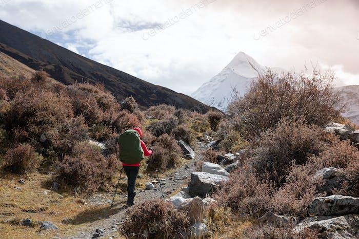 RunningWoman hiker hiking in winter mountains