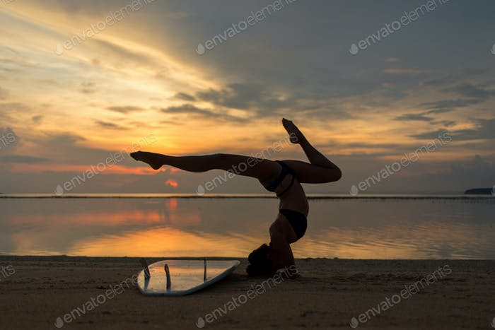 young flexible fit woman or girl posing on sandy beach