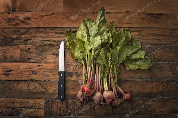 A handful of small beets, fresh organic vegetables harvested for the table. A vegetable knife.