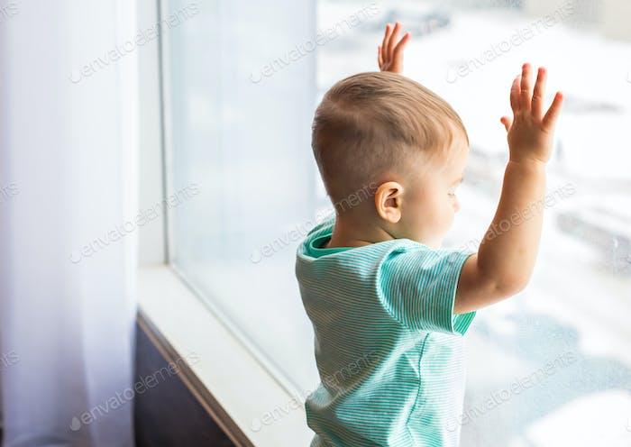 Улыбающийся ребенок, стоящий в комнате дома возле окна