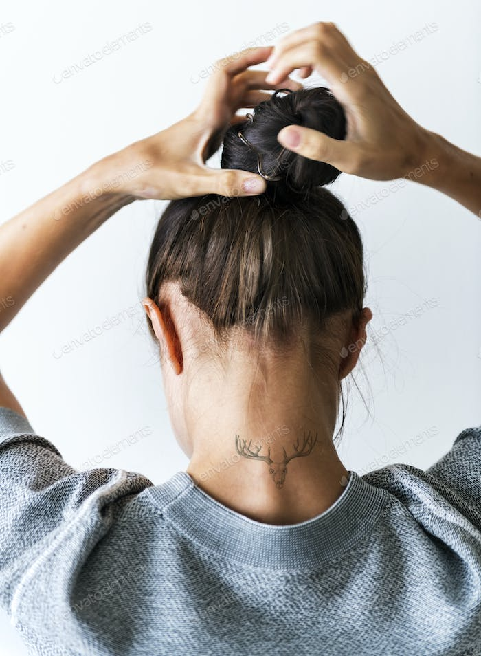 Woman putting her hair up in a bun