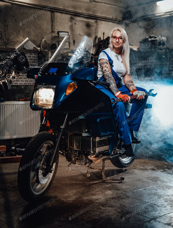 Blond woman mechanic in work overalls hold big wrench while sitting on sportbike in garage