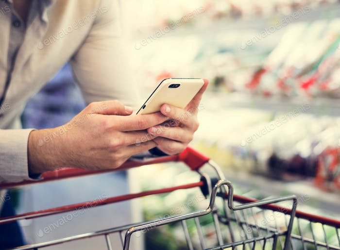 Man playing with his phone at supermarket