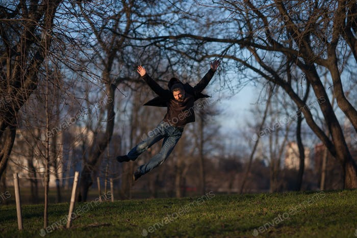 An elderly man jumps high while walking in the park.