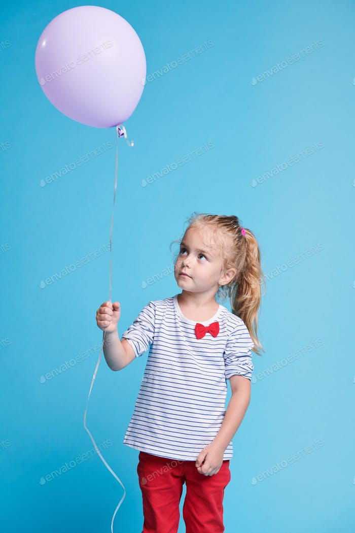 Adorable blonde little girl looking at single white balloon