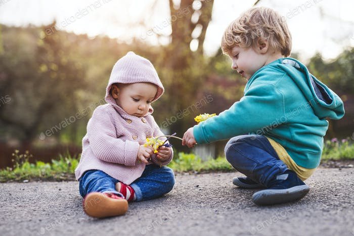 A toddler boy and girl outside on a spring walk.