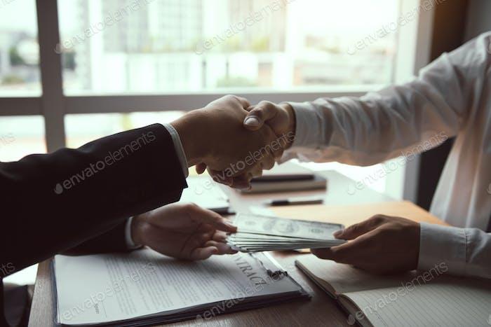 empresarios Corporativa estrecharme la mano mientras un hombre da dinero y recibe dinero en efectivo