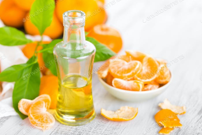Tangerines with leaves and bottle of essential citrus oil on a white background