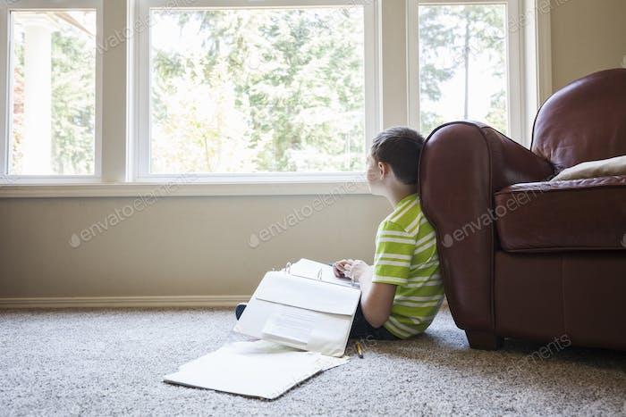 Kleiner Junge zu Hause macht Hausaufgaben.