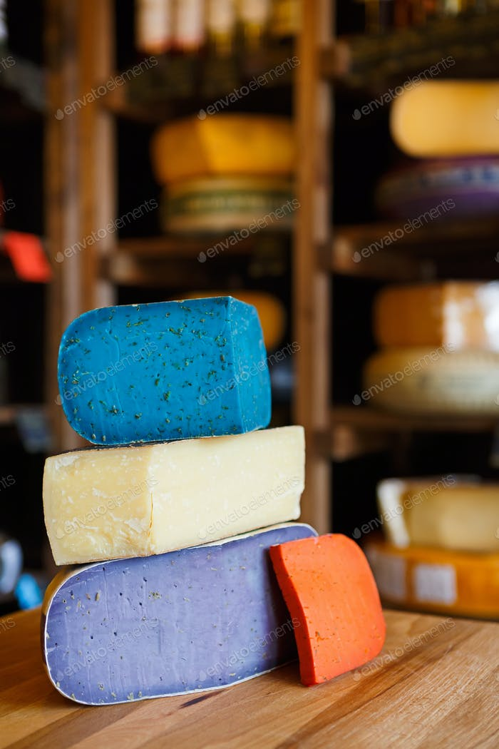 Gouda pesto cheese assortment. Lavender, blue, violet and red at grocery shop background
