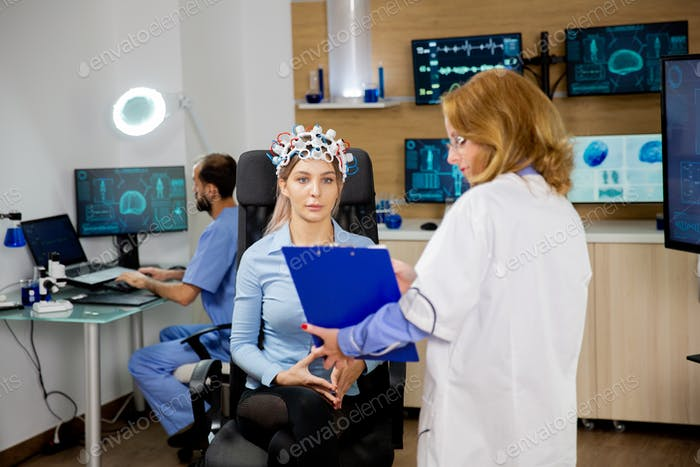 Patient woman scanning her brain and looking at a clipboard
