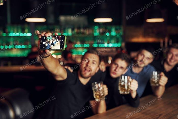 Einen Selfie machen. Drei Freunde ruhen in der Kneipe mit Bier in der Hand. Konversation haben
