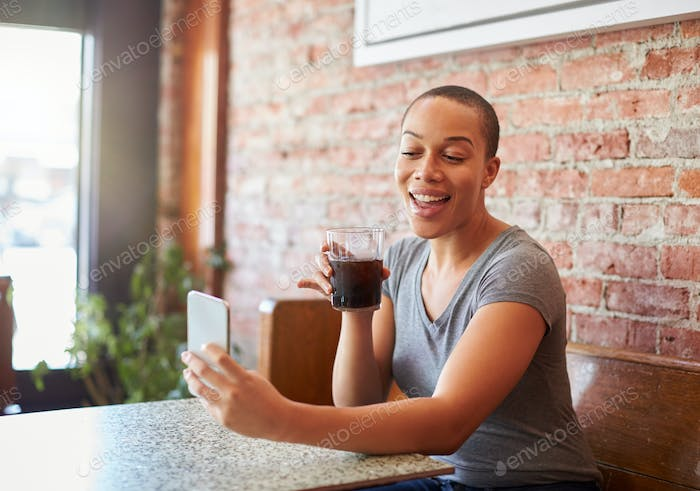 Woman Making Video Call On Mobile Phone Sitting In Coffee Shop