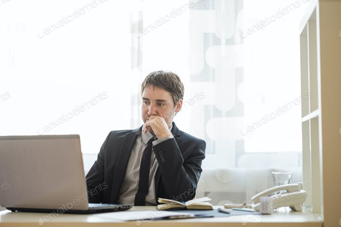 Young businessman working on laptop computer in his office