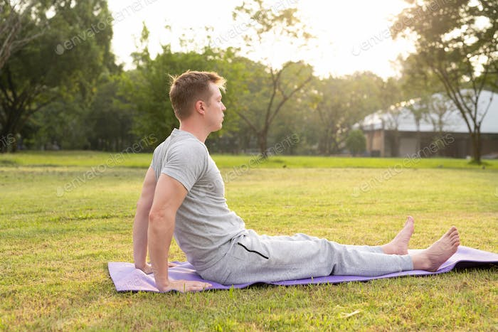 Profile view of young handsome man doing yoga at the park