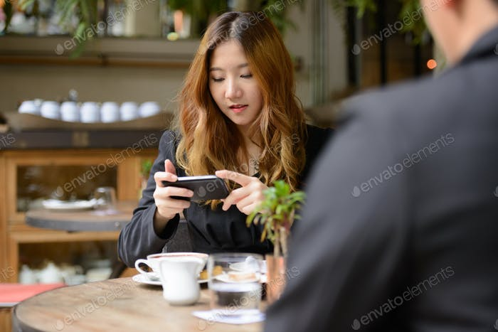 Young Asian business couple together at the coffee shop with woman using phone