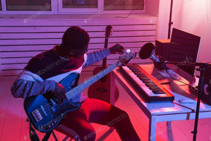 Create music and a recording studio concept - Black man guitarist recording electric bass guitar