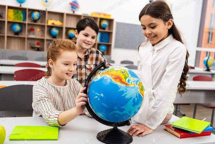 Three cheerful pupils playing with globe in classroom during geography lesson