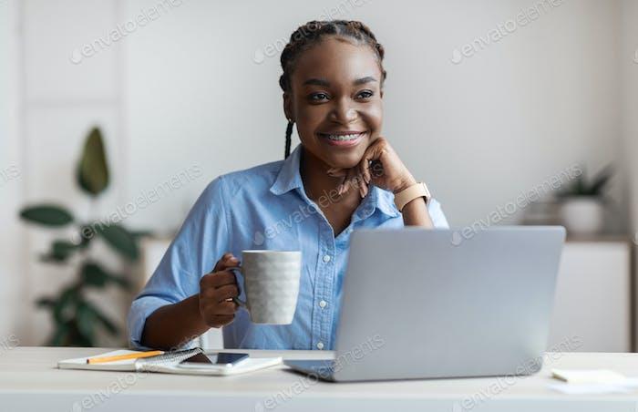 Nachdenkliche junge schwarze Freiberuflerin trinkt Kaffee am Arbeitsplatz im Home Office