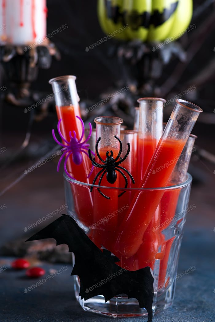 Bloody cocktail in glass tubes for Halloween party celebration. Black stone background