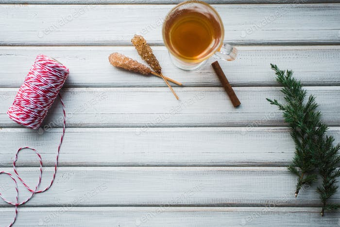 Cup of tea and cane sugar. On wooden background.