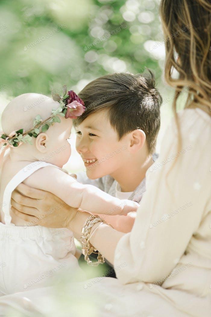 Uma mulher e dois filhos, um menino cumprimentando uma menina. Retrato de família.