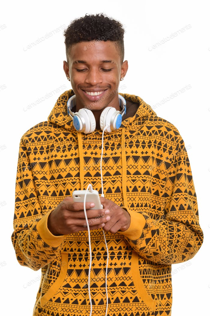 Young happy African man using mobile phone while wearing headpho