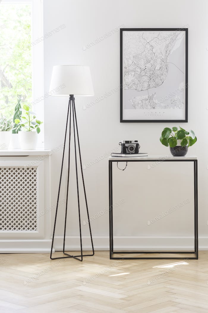 Minimalist office interior with a black lamp, table and map in a