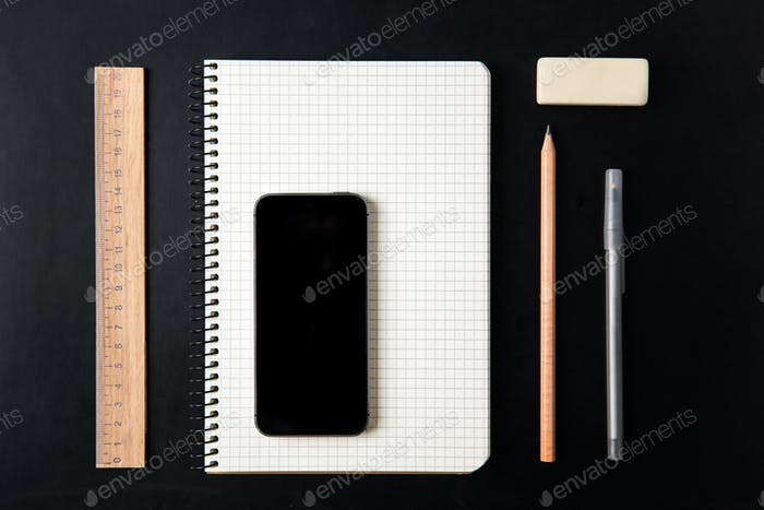 Top view of school supplies and blank screen mobile phone