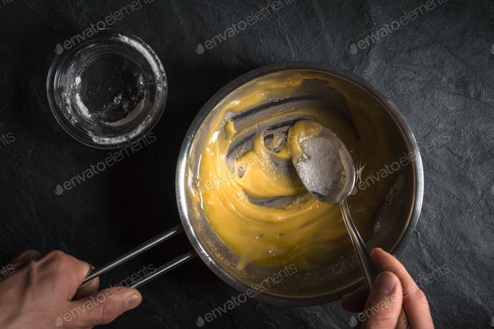 Adding flour to the melted butter on a gray table