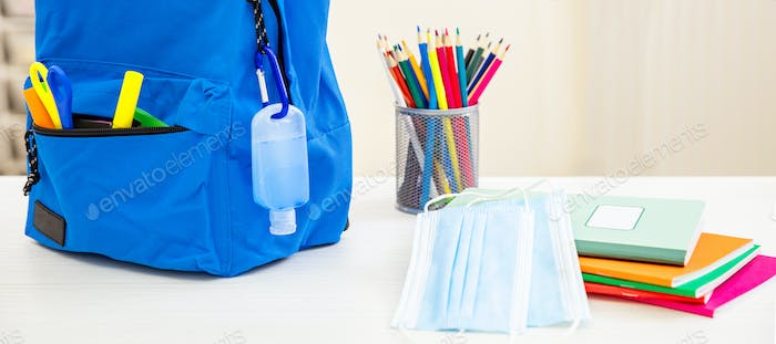 School, coronavirus days. COVID 19 protecton, hand sanitizer gel and backpack on student desk
