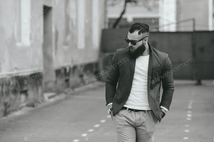 Stylish bearded man walks through the city