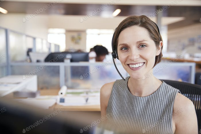 Young white woman working in a call centre smiling to camera