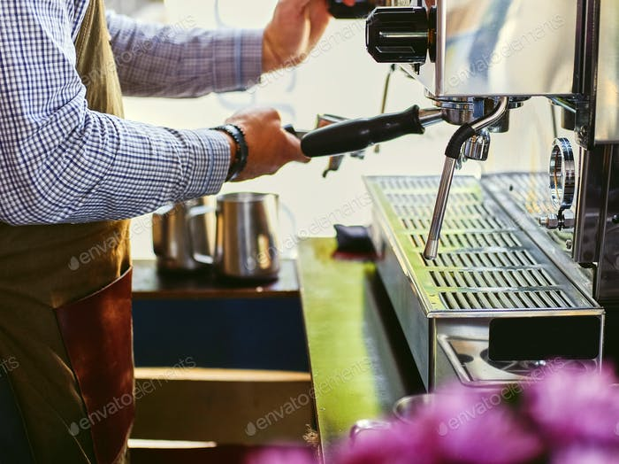 Close up image of a man preparing coffee late.