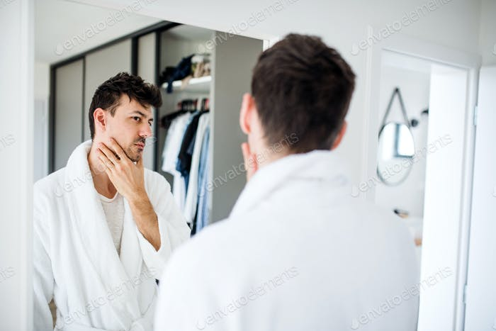 Young man looking in mirror in bedroom in the morning, daily routine