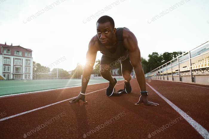 Fit confident african sportsman standing in starting position