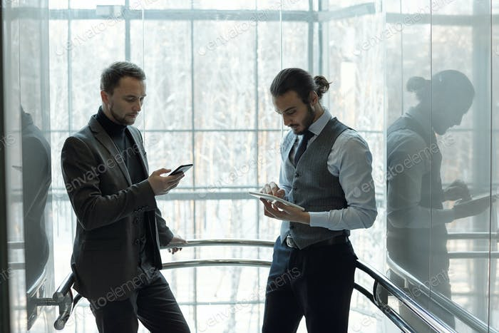 Two young serious businessmen in formalwear using mobile gadgets