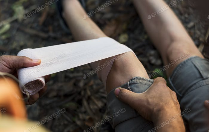 Mann legt Bandage auf das Knie seines Partners im Dschungel