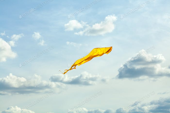 Bright yellow kite flies in the wind, blue cloudy sky background. Summer recreation concept.