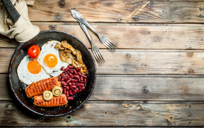 English breakfast.Fried eggs with sausages, mushrooms and beans.
